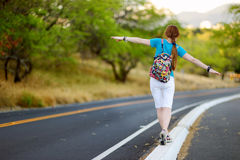 Young tourist hitchhiking along a road Stock Photo