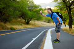 Young tourist hitchhiking along a road. Young tourist with a backpack hitchhiking along a road Stock Photography