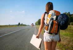 Young tourist hitchhiking along a road. With message board Stock Photo