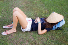 Young tourist lady lying on green grass sleeping Royalty Free Stock Photography