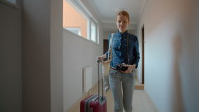Young Tourist is Leaving the Apartment and Going with a Suitcase to the Elevator. Young Beautiful Tourist Girl is Leaving the Apartment and Going with a Suitcase stock video footage