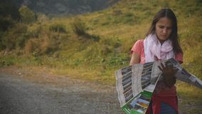 A young tourist is looking for a road, studying the map of Altai during the trip stock footage