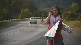A young tourist is looking for a road, studying the map of Altai during the trip stock video