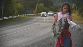 A young tourist is looking for a road, studying the map of Altai during the trip. Slow-motion shooting stock video
