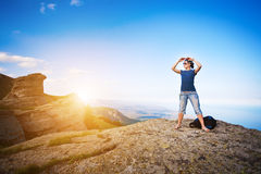 Young tourist looks for way from the rocks top Stock Photography