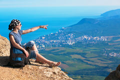 Young tourist looks for way from the rocks top Stock Images