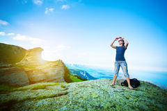 Young tourist looks for way from the rocks top Royalty Free Stock Image