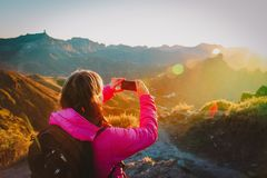 Young tourist making mobile phone photo of sunset in mountains. Travel concept royalty free stock photography