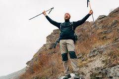Young tourist male hiking in mountains, finished his track, feels happy. Traveler bearded man mountaineering during his journey. Young tourist male hiking in stock images