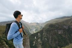 Tourist man with a backpack against the Caucasus Mountains stock images