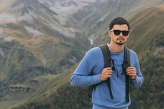 Tourist man with a backpack against the Caucasus Mountains stock photography