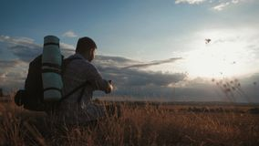 A young tourist man with a backpack uses a mobile phone. In the rays of the setting sun. Travel concept. Always online. stock footage