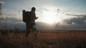 A young tourist man with a backpack uses a mobile phone. In the rays of the setting sun. Travel concept. Always online. stock video