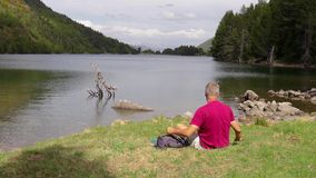 Young tourist man looking at the beautiful mountain lake in Spanish National Park Augestortes.  stock video footage