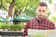 Young tourist man looking at a map. Portrait of a young handsome tourist man looking at a map. Tourism concept. Outdoors Royalty Free Stock Photo