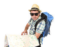 Young tourist man reading city map looking lost and confused loosing orientation carrying backpack. Wearing summer hat and sunglasses disoriented  face Royalty Free Stock Image
