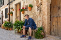Young tourist man sitting on the bench on medieval street Royalty Free Stock Image