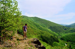 Young tourist man traveling in the green summer mountain stock image