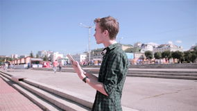Young tourist man using map on his tablet walking in the city. stock footage