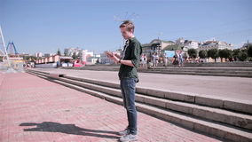 Young tourist man using map on his tablet walking in the city. HD stock video