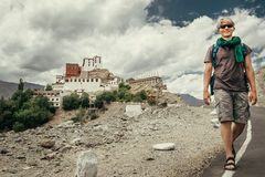 Young tourist man walks on road near Thiksey Monastery in India, Royalty Free Stock Photos