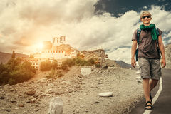 Young tourist man walks on road near Thiksey Monastery in India, Stock Photo