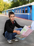 Young tourist with a map. Young tourist sitting near the train and  looking landmark on the map Stock Images
