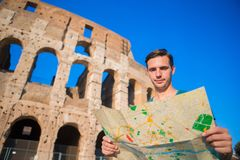 Young tourist with map in front of Colosseum. Young man searching the attraction background the famous area in Rome Royalty Free Stock Photography