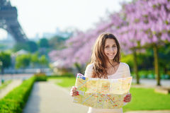 Young tourist with map near the Eiffel tower. Young beautiful female tourist with map near the Eiffel tower in Paris, looking for the direction Royalty Free Stock Photos