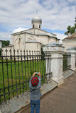 Young tourist photographer. Young girl photographing an old Russian church in Novgorod, Russia Royalty Free Stock Image