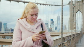 Young tourist in a pink coat uses a smartphone. stock video footage