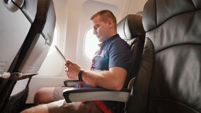 A young tourist on the plane works with the tablet before leaving. A young tourist on the plane works with the tablet before leaving stock footage