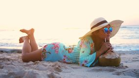 Young tourist pretty woman in sunglasses and the hat lying on tropical paradise sandy beach and drinks coconut juice Stock Photo