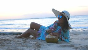 Young tourist pretty woman in sunglasses and the hat lying on tropical paradise sandy beach and drinks coconut juice Royalty Free Stock Image