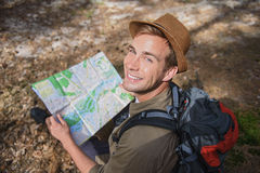Young tourist is ready to travel. Cheerful male traveler is reading a map with joy. He is sitting and looking at camera happily. Man is smiling Stock Image