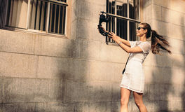 Young tourist recording selfie video while walking in the street. Fashion vlogger recording content for her vlog. Young woman taking selfie in a street using a Stock Photos