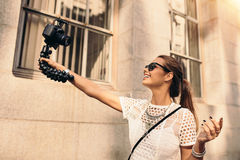 Young tourist recording selfie video while walking in the street. Female Vlogger recording content for her vlog. Young woman taking selfie in a street using a Royalty Free Stock Photos