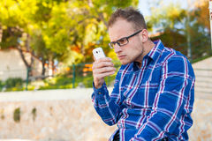 Young tourist in shirt with mobile phone on a Croatian beach. Royalty Free Stock Images