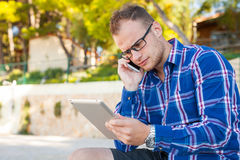 Young tourist in shirt with mobile phone and tablet pc on a Croa Royalty Free Stock Photos
