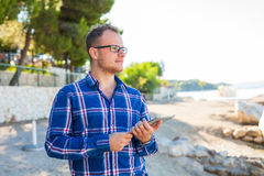 Young tourist in shirt with mobile tablet pc on a beach. Positiv Royalty Free Stock Photography