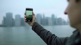 Young tourist shooting Manhattan island on his smartphone camera stock footage