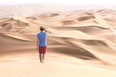 Young tourist in shorts hiking in giant dunes. Young handsome caucasian tourist in shorts and straq hat hiking in Liwa desert dunes. Abu Dhabi, UAE Stock Photography