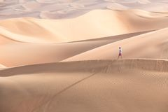 Young tourist in shorts hiking in giant dunes. Young handsome caucasian tourist in shorts and straq hat hiking in Liwa desert dunes. Abu Dhabi, UAE Stock Images