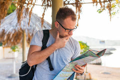 Young tourist sitting under palm tree and looking at the map. Po Stock Image