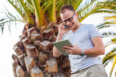 Young tourist sitting under palm tree with mobile phone and list Royalty Free Stock Photo