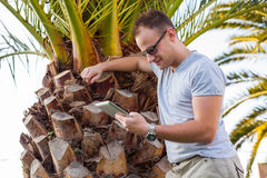 Young tourist sitting under palm tree with mobile phone and list Stock Photos