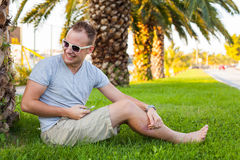 Young tourist sitting under palm tree with mobile phone. Positiv Stock Photography