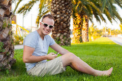 Young tourist sitting under palm tree with mobile phone. Positiv Stock Images