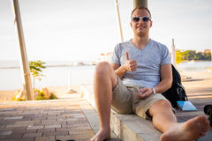 Young tourist sitting under palm tree with mobile phone. Positiv Stock Photo