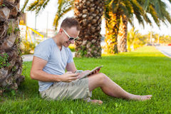 Young tourist sitting under palm tree with mobile phone and tabl Stock Images